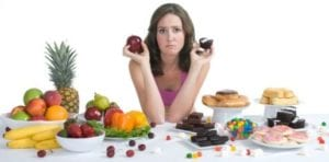 woman choosing between junk food and healthy